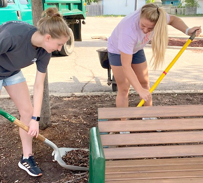 """Riley Mullin, a junior at Mendon High School, and Anna Smith, a senior, were part of a 21-person team that helped to clean and beautify downtown Mendon. The annual project is a part of National Honor Society's """"Volunteer Day."""""""