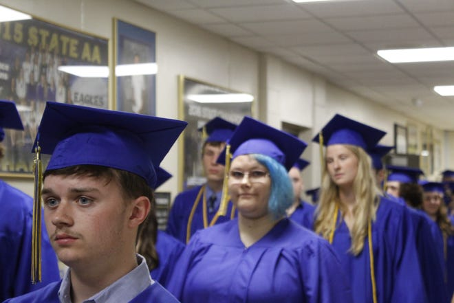 Central High School graduates Ashton Davis, Daria Davies and Morgan Dannon wait in line to enter Golden Eagles Arena before Sunday's ceremony.