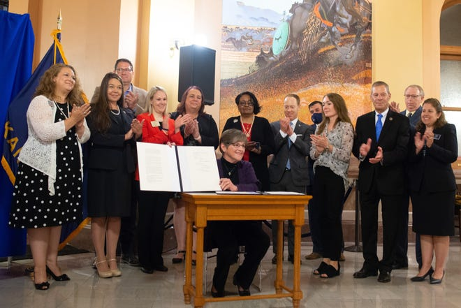 Gov. Laura Kelly smiles while surrounded by a bipartisan group of lawmakers and advocates after signing a deal to fund Kansas schools during a ceremony Monday in the Kansas Statehouse.