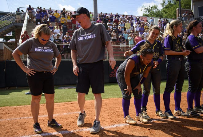 Jack Britt softball coaches Sebrina Wilson and Joe Myrtle share a laugh just before the team is presented with trophies for winning the 2018 state 4-A softball championship at NC State's Dail Softball Stadium in Raleigh. Both are stepping down as coaches after starting Britt's softball program when the school opened in 2000.