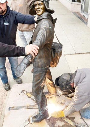 """Josh Craig from #1 Welding secures """"Paper Boy,"""" by artists Lee Leuning and Sherri Treeby, at 211 E. Kemp."""