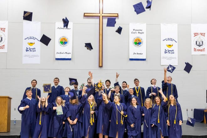 Graduates of Great Plains Lutheran High School toss their caps in the air. The ceremony was Saturday.