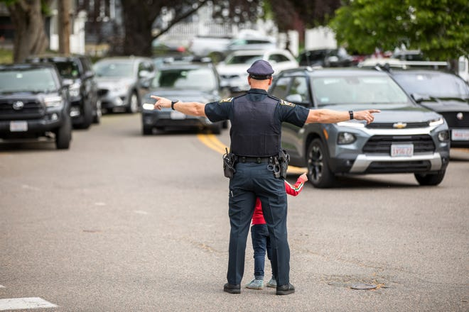 Swampscott Police Officer Kevin Reen and  Ethan Fontes-Fried, 3, perform crossing-guard duty near the Stanley Elementary School on Friday, May 21, 2021.