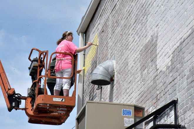 Viktorea Sims and Kimber Thompson paint a mural at Albion Malleable Brewing Company in downtown Albion on Tuesday, May 18, 2021.
