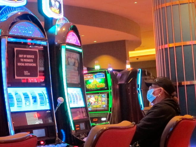 An intentionally disabled slot machine is next to a woman playing a different slot machine May 3, 2021, at the Hard Rock casino in Atlantic City, N.J.