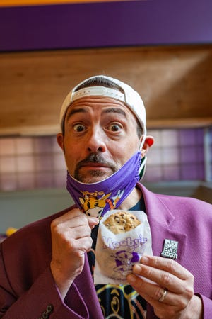 """Director Kevin Smith, holding the """"Cookies from the Mall"""" sold at Mooby's restaurant pop-ups. Smith started the pop-ups, based on a fictional restaurant in his movies, during the pandemic."""