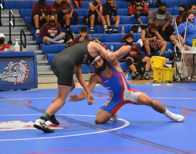 Las Cruces High's Christopher Ochoa goes in for the leg of Gadsden's Anthony Alvarez during Saturday's 132 pound class District  3-5A match.