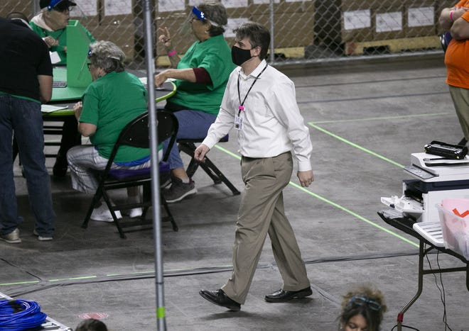 Cyber Ninjas CEO Doug Logan walks around the Coliseum floor as Maricopa County ballots from the 2020 general election are examined and recounted by contractors hired by the Arizona Senate in an audit at the Veterans Memorial Coliseum in Phoenix on May 24, 2021. Cyber Ninjas is the contracting firm hired to handle the audit.