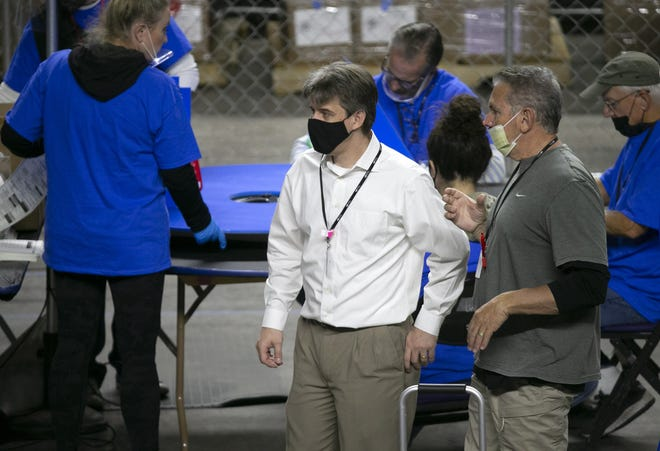 Cyber Ninjas CEO Doug Logan (center) walks around the coliseum floor as Maricopa County ballots from the 2020 general election are examined and recounted by contractors hired by the Arizona Senate in an audit at the Veterans Memorial Coliseum in Phoenix on May 24, 2021. Cyber Ninjas is the contracting firm hired to handle the audit.