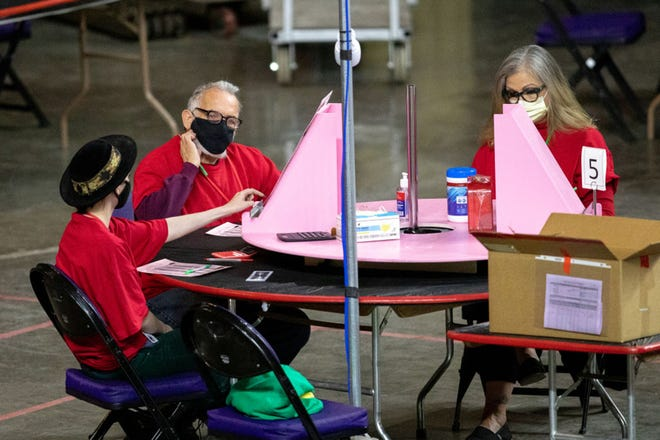 Contractors working for Cyber Ninjas, who was hired by the Arizona State Senate, examine and recount ballots from the 2020 general election at Veterans Memorial Coliseum on May 1, 2021 in Phoenix, Arizona. (Courtney Pedroza/Getty Images/TNS)