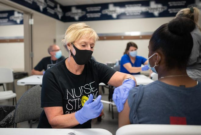 McKinney Independent School District registered nurse Nancy Yarbrough administers a COVID-19 vaccine to a student at McKinney ISD Stadium and Community Event Center on Thursday.