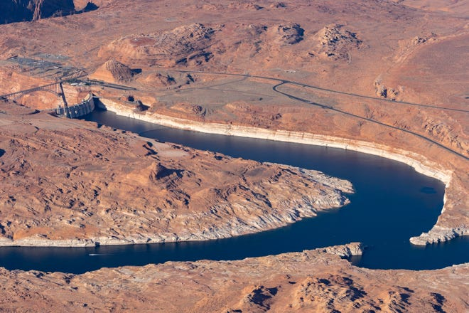 An aerial shot of the Colorado River at Lake Powell near Page, AZ shows the site where Utah's Lake Powell Pipeline plans to tap into the water source just upstream of the Glen Canyon Dam, for transport to Sand Hollow Reservoir. The white bands of rock along the river edges, left by mineral deposits from past water contact, show how much the river level has dropped in recent years.