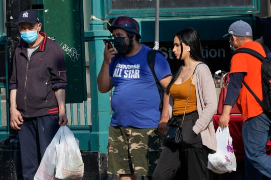 Pedestrians wear protective masks during the coronavirus pandemic Wednesday, May 19, 2021, in the Queens borough of New York. New York eased its mask and social distancing mandates again Wednesday, however, masks are still required for everyone in many settings. (AP Photo/Frank Franklin II)