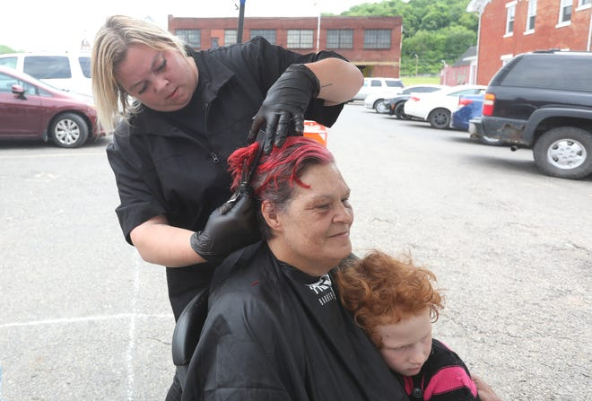 Janis Yarus gets a hug from her great-niece Rayliah Sutles, 5, while getting a haircut from Jesica Holland. Holland is a student at Prince's Barber Academy, and was among a group of students giving free haircuts outside Christ's Table on Monday. Prince's Barber Academy, located at 330 Main St., is offering walk-in haircuts Tuesday through Saturday, from 8 am to 4 pm. For more information, visit www.princesbarberacademy.com.