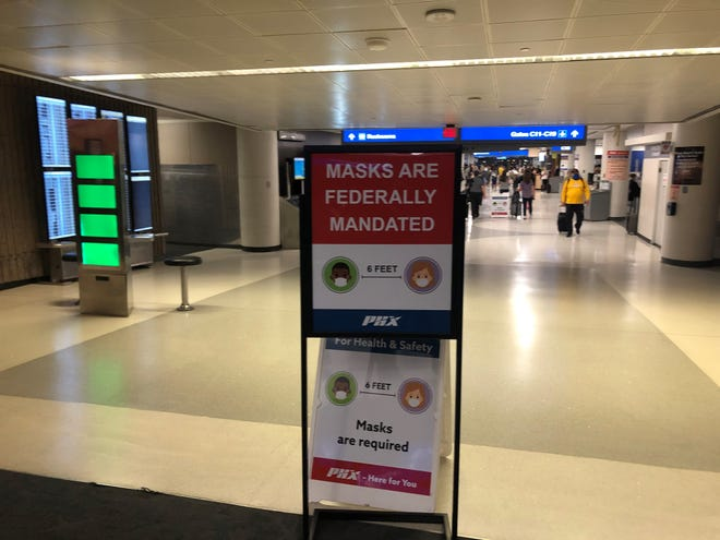 A sign at Phoenix Sky Harbor International Airport reminds travelers that face masks are required.