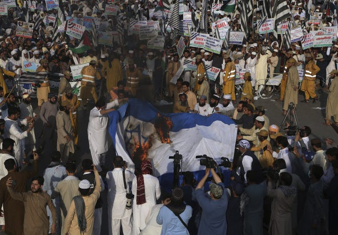 Supporters of a Pakistani religious group burn a representation of an Israeli flag during a rally in support of Palestinians, in Peshawar, Pakistan, Friday. [AP PHOTO/MUHAMMAD SAJJAD]