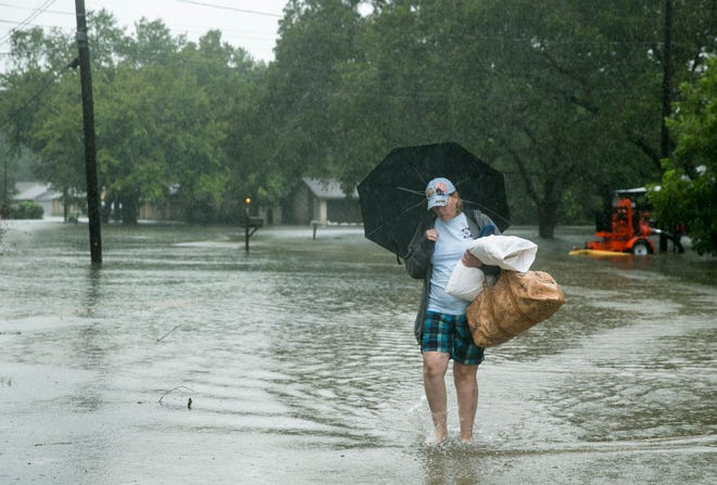 Jeannie Ralph carries belongings from her house on NE Seventh Street in Smithville after Hurricane Harvey on Aug. 26, 2017.  Last week, the Texas General Land Office approved more than $28 million to improve flood mitigation infrastructure throughout Bastrop County.