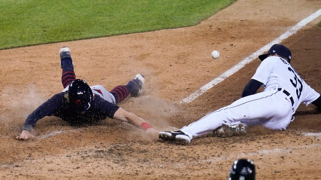 Cleveland's Owen Miller scores as Detroit Tigers relief pitcher Bryan Garcia (33) covers home plate after a wild pitch in the seventh inning of a baseball game in Detroit, Monday, May 24, 2021. (AP Photo/Paul Sancya)