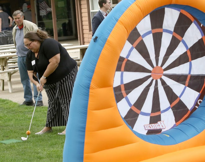 Lanny Snode from Tannanhauf Golf Course, left, watches as YWCA Director Stacie Weimer hits a tennis ball toward a large target May 6 during the Alliance Chamber of Commerce's first Business After Hours mixer since February 2020.