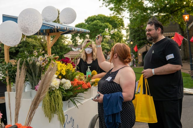 Jennifer Uetz and Matt Hartley check out flower samples at the Pretty Pedals Flower Cart, one of the Peddler's Village Outdoor Wedding Show exhibits on Friday in Buckingham.