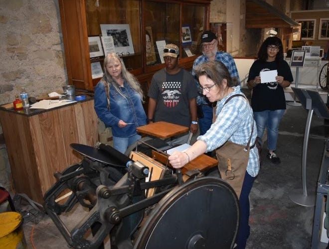 Jayne Johnson, an artist and print-maker from North Carolina, operates the Brown County Museum of History's nearly-century-old printing press during the 'Great SneaK Peak' Saturday afternoon at the museum.