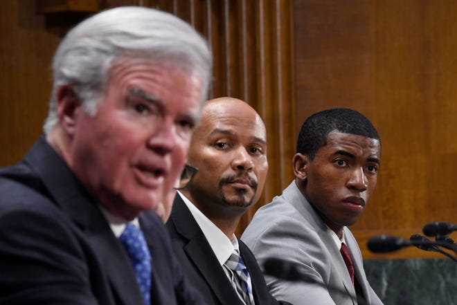 National Collegiate Athletic Association Student-Athlete Advisory Committee Chair Kendall Spencer, right, and National College Players Association Executive Director Ramogi Huma, center, listen as NCAA President Mark Emmert, left, testifies during a Senate Commerce subcommittee hearing on Feb. 11, 2020, on intercollegiate athlete compensation.