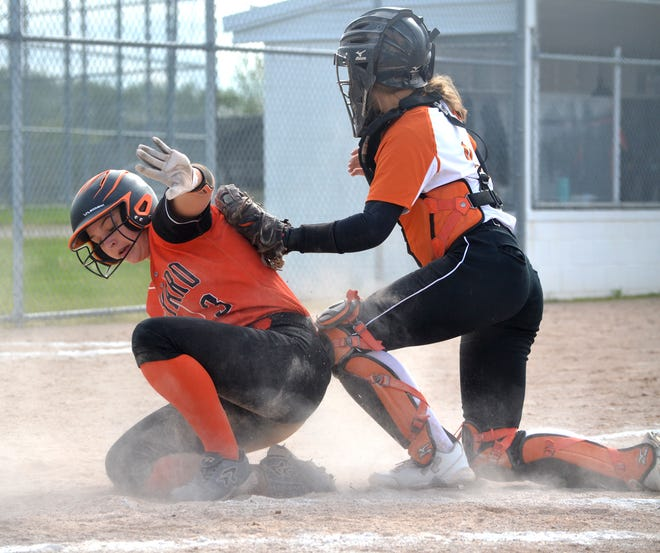 Rudyard's Paige Postma, left, just slides in safely at home while Cheboygan catcher Marley Couture applies a tag during the top of the eighth inning in game one of a Straits Area Conference varsity softball doubleheader in Cheboygan on Monday.