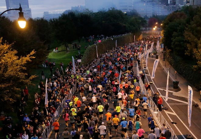 Runners move down Long Street past North Bank Park during the Nationwide Children's Hospital Columbus Marathon and 1/2 Marathon in Downtown Columbus in 2019.