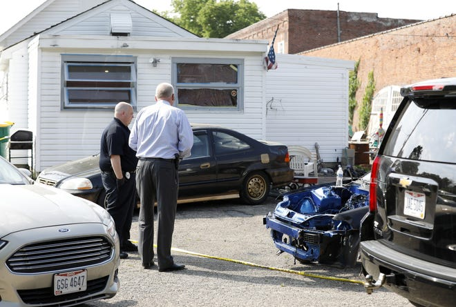 Investigators look over a crime scene outside a West jefferson apartment house, where four people were killed Monday.