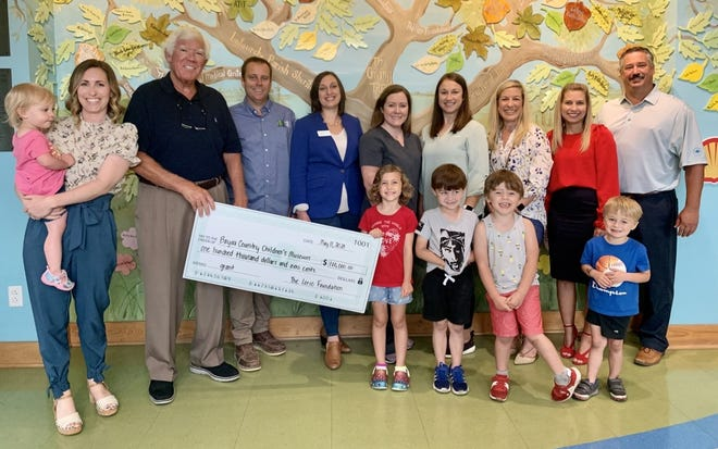 Lorio Foundation Executive Director Cam Morvant delivers a $100,000 check to the Bayou Country Children's Museum in Thibodaux.