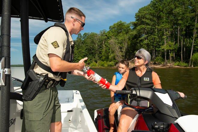 Officer John Sprowl checks a jet skier's license and safety equipment on Jordan Lake.