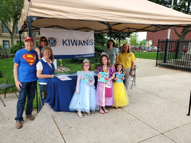 """Kiwanis members Bob Heinton, Cheryl Rayburn, Gayle Heinton, LaDawn Spring, and President Sharon George greeted these three princesses during the recently Day of Enchantment. Each princess and prince were given the book """"Empathy is your Super Power,"""" donated by the Cambridge Kiwanis Club. More than 75 books were distributed to those who participated."""