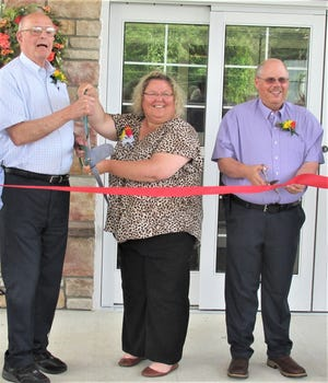 Danbury Senior Living founder and CEO Bill Lemmon (from left), Holmes County Chamber of Commerce Executive Director Tiffany Gerber, and Millersburg Mayor Jeff Huebner prepare to cut the ribbon to open the new Millersburg facility on Glen Drive Tuesday afternoon.