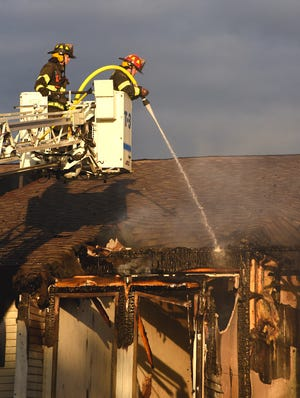 Eight different fire departments, including Ridgeway and Tecumseh, were on the scene of an apartment fire which broke out around 4:30 a.m. Sunday, May 23 at Village Pointe Apartments in Dundee. Above the ladder truck of Dundee Fire Department, are two Milan fireman maintaining the hot spots.