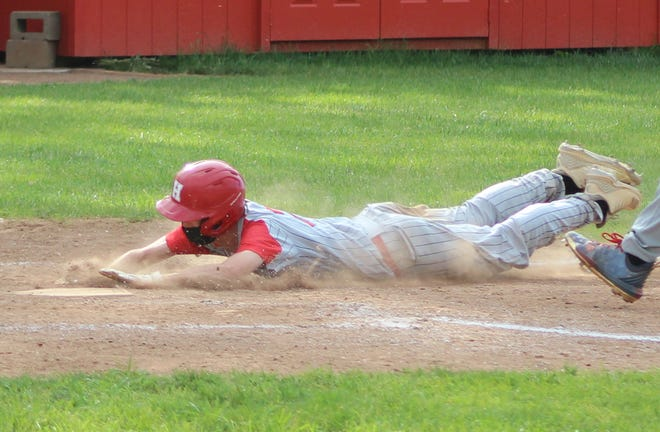 Hornell's Griffyn Baker slides into home on a passed ball during Monday's game in Dansville.