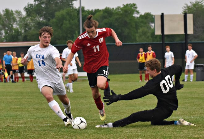Fort Madison's Xander Wellman (11) follows his shot that was deflected by Clear Creek-Amana goalkeeper Drew Streit (00) in the first half of Monday's Class 2A substate final at Baxter Sports Complex in Fort Madison's. The Clippers' Harrison Cory (14) is in pursuit.