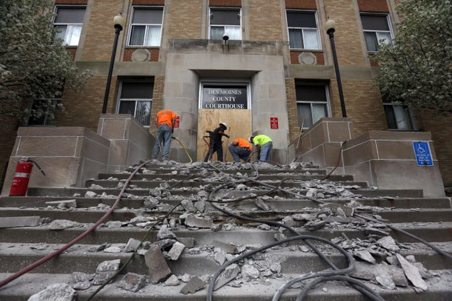 Workers with Abolt, Inc. Construction of Fort Madison use jack hammers and a shovel to tear up the existing steps April 28, 2014, in front of the Des Moines County Courthouse.