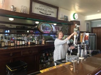 Marsha Anseeuw, co-owner of General Store Tap is seen behind the full bar with draft beers.