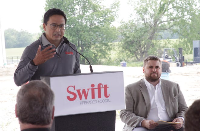 Tom Lopez, president and chief operating officer, Swift Prepared Foods, talks about company values and goals as it begins operations to produce ready-to-eat bacon products at its new facility in Moberly.  Shown seated is Moberly Area Economic Development Corporation President Michael Bugalski.