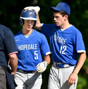 Hopedale's Zach Frohn (left) gets a pat on the head from teammate John McDonough after scoring a run during a game against Sutton at Hopedale Town Park, May 25, 2021.