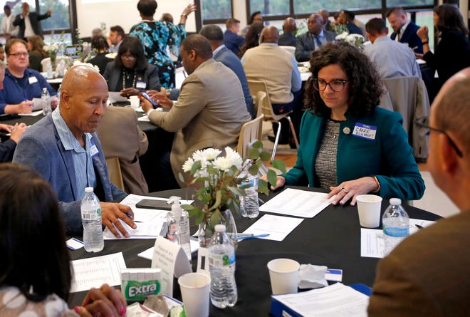 Garland Pruitt and Carrie Blumert talk during table discussions at the OK Justice Circle's Breaking Bread breakfast in May at Millwood High School in Oklahoma City.