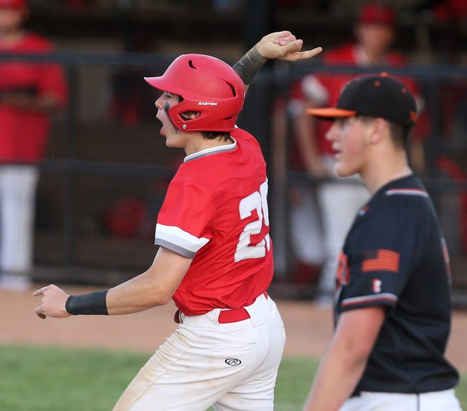AJ Pierson of Canton South celebrates after he and two of his teammates scored their Division II district semifinal game against Howland at Cene Park on Monday, May 24, 2021. At right, pitcher Braden Gebhardt of Howland walks back to the mound.