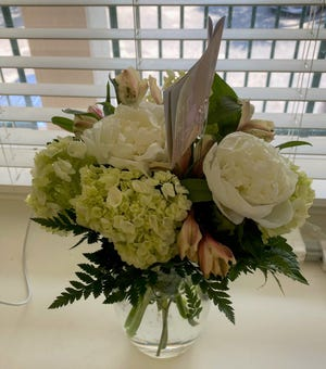 """This floral bouquet on the left cost $60 before tax, including delivery ($12). The client provided the vase. """"The arrangement should have cost $30 tops,"""" said BloomsyBox owner Juan Palacio."""