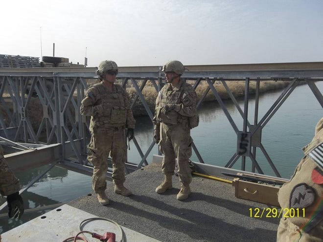 Erin Fagnan, right, talks to a fellow solider during a pre-convoy briefing in Afghanistan. She was deployed as a member of the South Dakota National Guard as part of Operation Enduring Freedom.