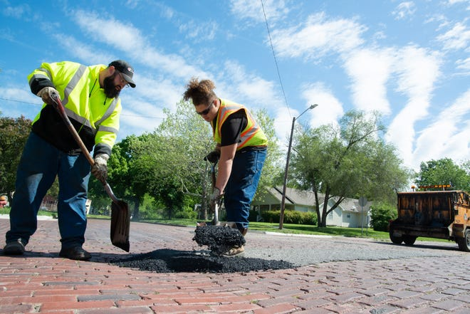 Public works employees Jacob Frost, left, works with Myles Wright to fill a pothole in mid-May at the intersection of S.W. Buchanan Street and S.W. Munson Avenue.