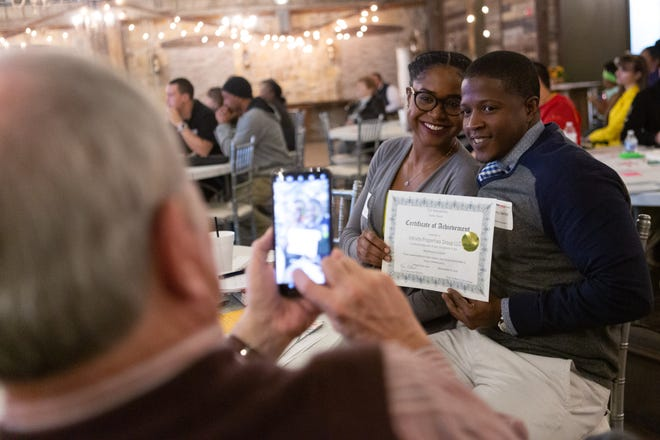 Mitch Miller takes a photo of Manny Herron and his wife, Del-Metrius Herron, after Manny accepted his Wheelhouse Incubator certificate at the program's 2019 graduation ceremony.