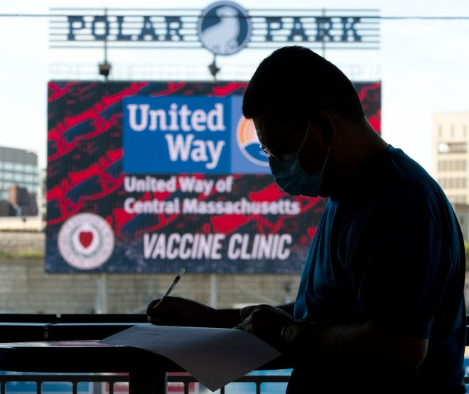 A man completes a registration form before receiving the COVID-19 vaccine at Polar Park May 25.