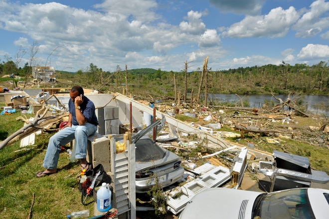June 2011 tornado:  Sitting on the foundation of his tornado-ravaged home on Wales Road in Brimfield, Francisco Gonzalez talks on his cell phone on Monday, June 6, 2011.