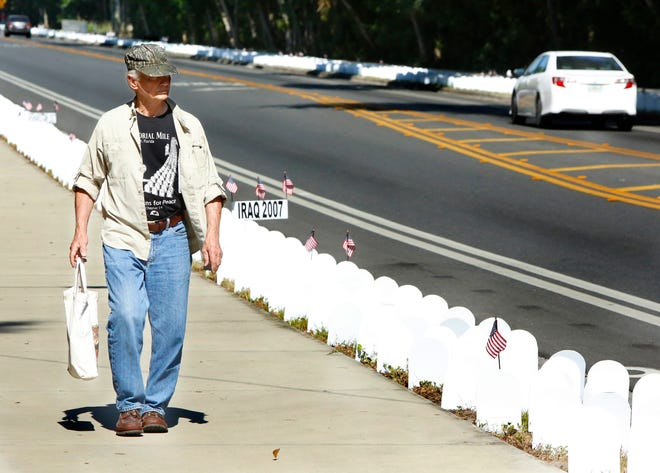 Randy Kaufman, an Army veteran of the Vietnam War, walks past the personalized tombstones in the annual Memorial Mile set up by Veterans For Peace along Northwest Eighth Avenue in Gainesville in 2019.