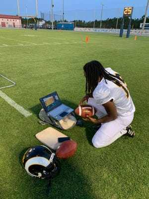 During a spring football game for Rutherford High School, junior Jonathan Walker watches an award ceremony where he won a full science scholarship to Florida Institute of Technology.